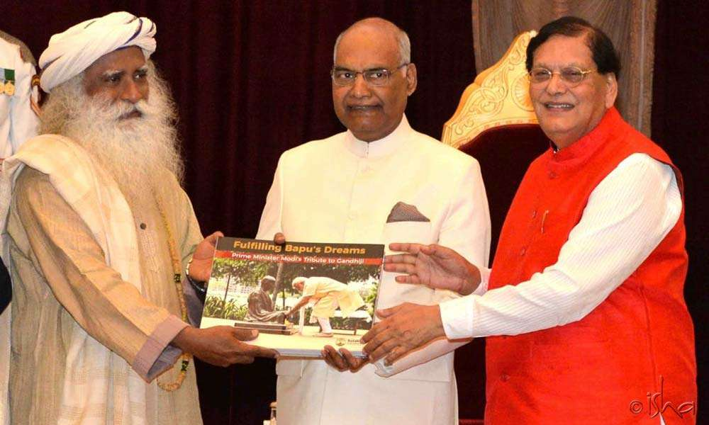 "Sadhguru presenting the first copy of ""Fulfilling Bapu's Dreams"" to Hon'ble President of India, Shri Ram Nath Kovind"