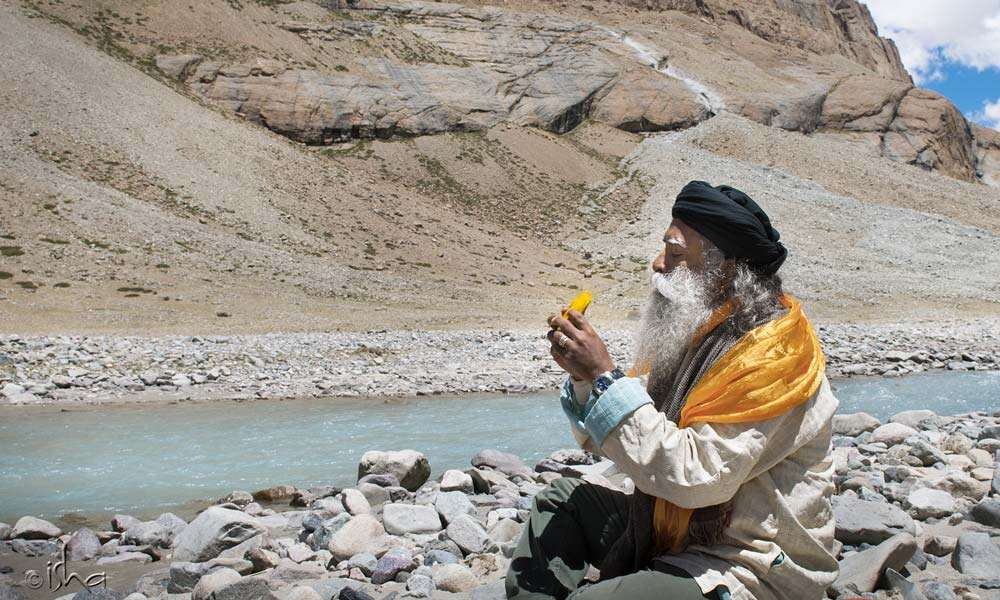Sadhguru eating a mango near Kailash
