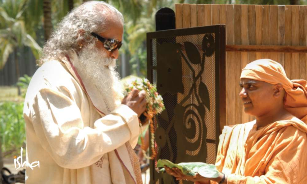 on-the-path-of-the-divine-maa-chandrahasa-maa-offering-flowers-to-sadhguru