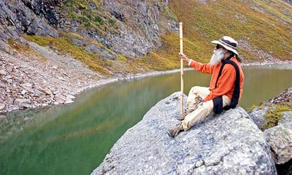 Sadhguru sitting on an outcrop of a rock at the Kantisarovar, Himalayas