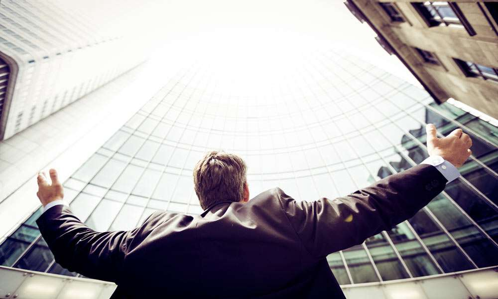 A Businessman looking up a skyscraper
