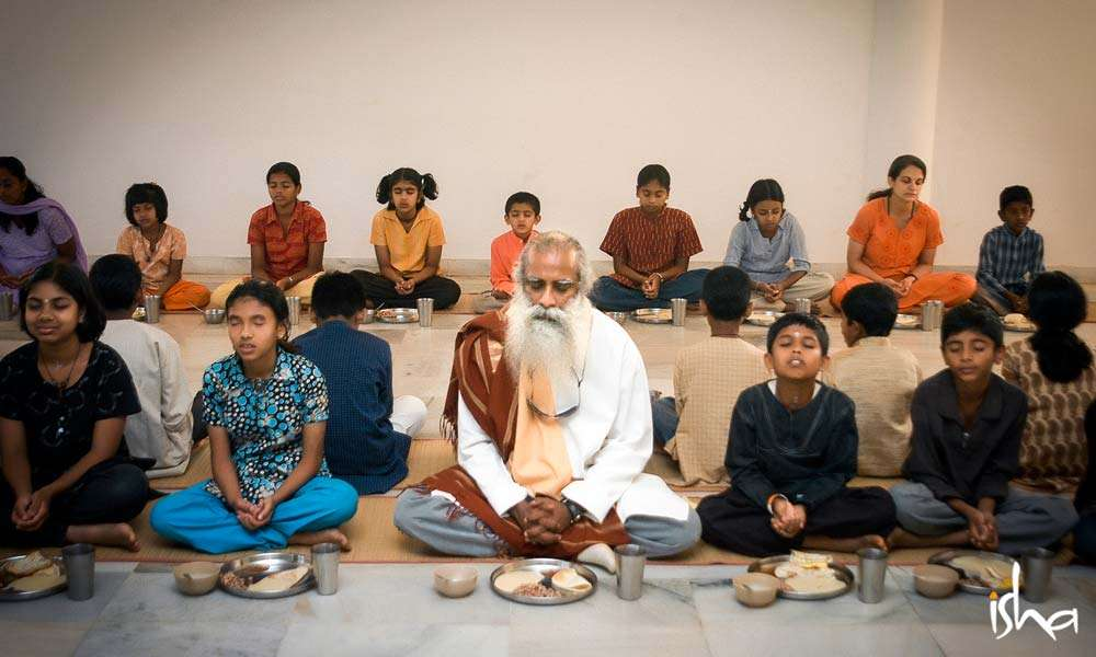 Sadhguru along with Isha Home School students saying the invocation before eating at Bhiksha Hall
