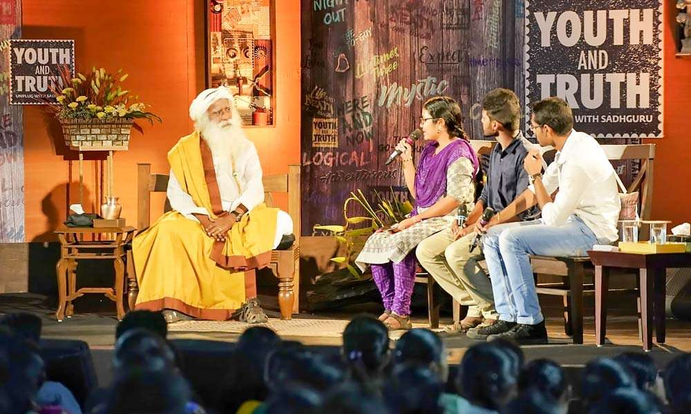 Sadhguru on stage with the three student moderators from Tamil Nadu Agricultural University | The Pulse of Youth AND Truth – TNAU