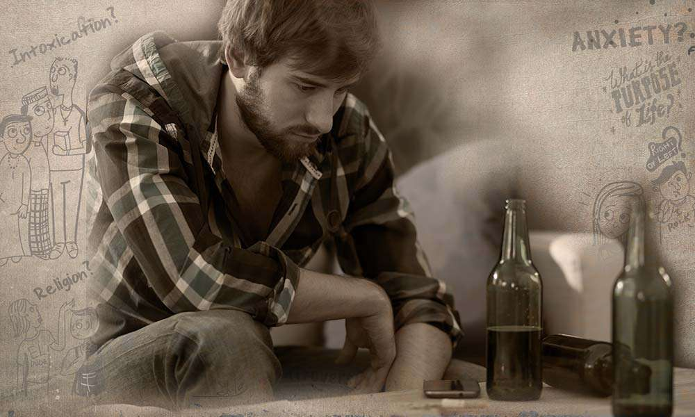 A depressed young man sitting on a couch with alcohol before him | Why Are Youth Turning to Alcohol and Drugs?