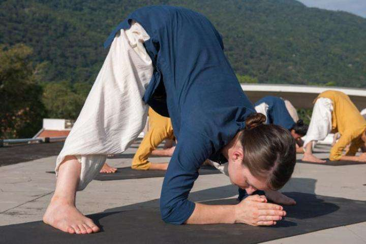 Hata Yoga School participant doing angamardana in organic cotton clothing