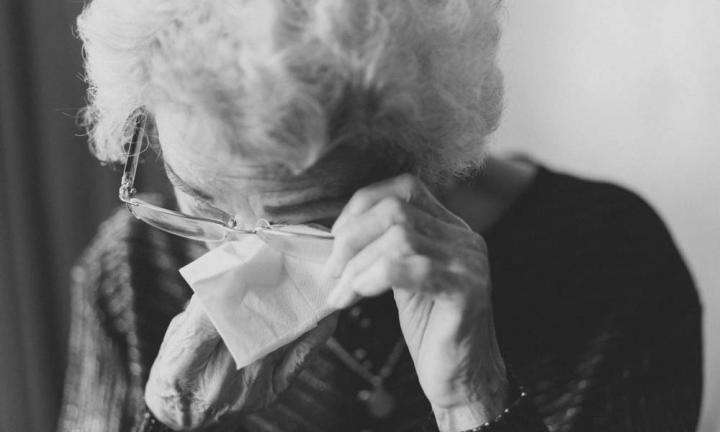 An elderly lady wiping her eyes with a tissue | How To Deal With The Loss of a Loved One