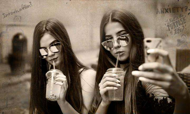 Two girls having a cold drink and taking selfie | Is it Wrong to Seek Attention Through Social Media?