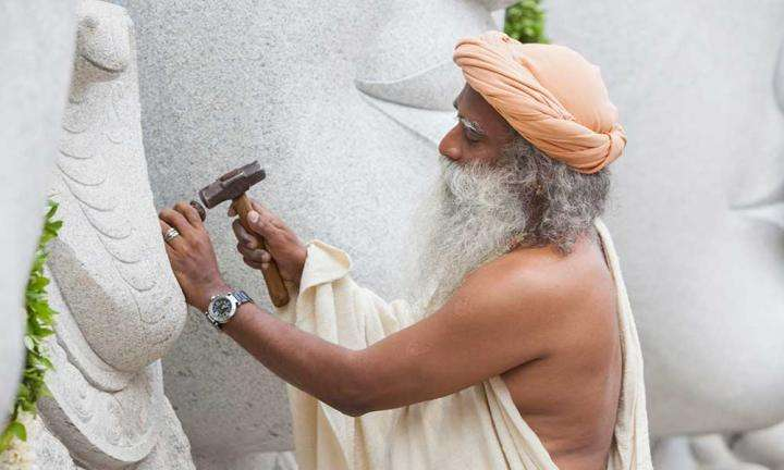 Sadhguru working with a chisel and hammer at the Trimurti panel, Isha Yoga Center | What Sort of Architecture Should Modern India Create?