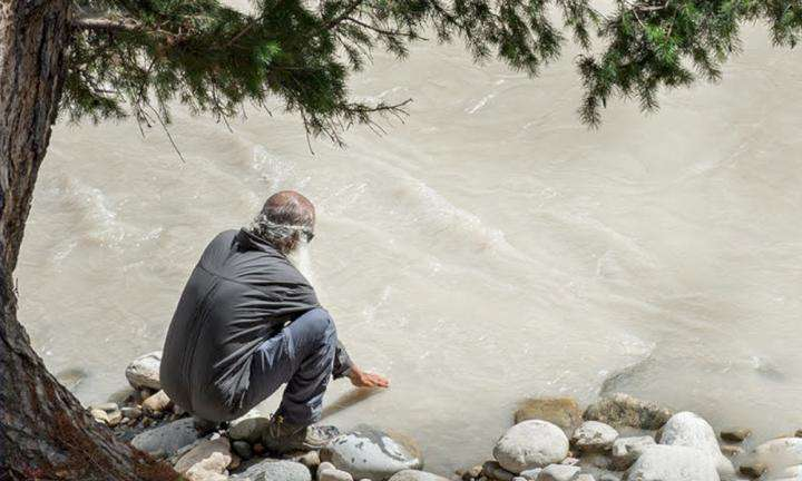 sadhguru wisdom article | Water Scarcity Is The Real Problem, Not Water Pollution | Sadhguru touching a flowing river